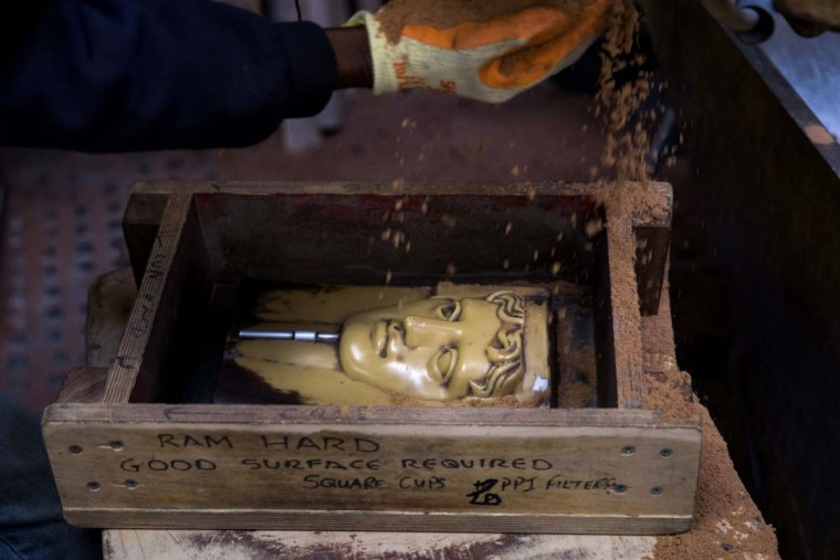 A moulder pours sand over a form to make a cast for a BAFTA (British Academy of Film and Television Arts) mask, as they are cast during a photocall at the New Pro Foundries, west of London on January 31, 2017. The masks will be presented to winners at BAFTA's awards ceremony in London on February 12, 2017. (DANIEL LEAL-OLIVAS/AFP/Getty Images)