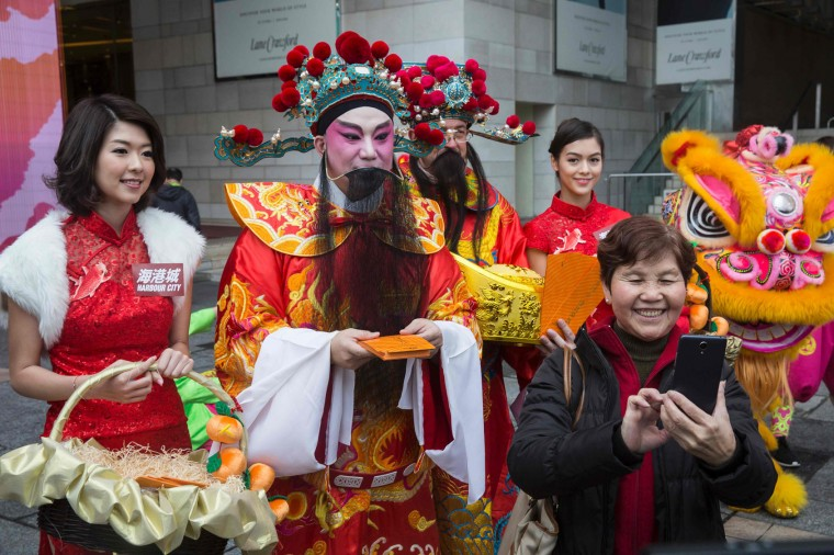 "This picture taken on January 16, 2017 shows a woman (R) taking a selfie with a man (C) in traditional Chinese dress as he hands out ""laicee"" packets in Hong Kong for the Year of the Rooster as the 2017 Lunar New Year approaches. US President Donald Trump will strut through the Year of the Rooster, thriving as Hong Kong geomancers predict 2017 will be marked by the arguments and aggression -- characteristics attributed to the animal. (Isaac Lawrence/AFP/Getty Images)"