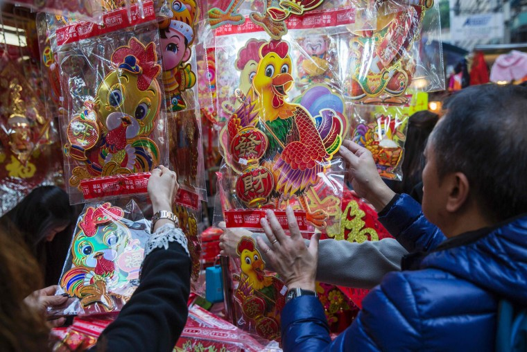 This picture taken on January 21, 2017 shows people looking at a stall in Hong Kong selling decorations for the Year of the Rooster as the 2017 Lunar New Year approaches. US President Donald Trump will strut through the Year of the Rooster, thriving as Hong Kong geomancers predict 2017 will be marked by the arguments and aggression -- characteristics attributed to the animal. (Isaac Lawrence/AFP/Getty Images)