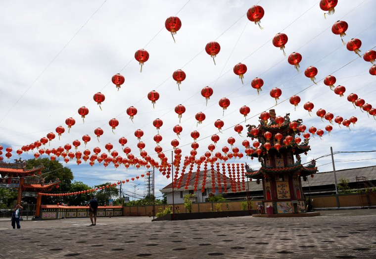 "A man (L) takes picture of lanterns decorating a Chinese temple ahead of the Lunar New Year festival in Denpasar, on Indonesia's Bali island on January 23, 2017. Indonesian-Chinese are preparing to celebrate the Lunar New Year or ""Spring Festival, which falls on January 28 this year, for the start of the Year of the Rooster. (Sonny Tumbelaka/AFP/Getty Images)"