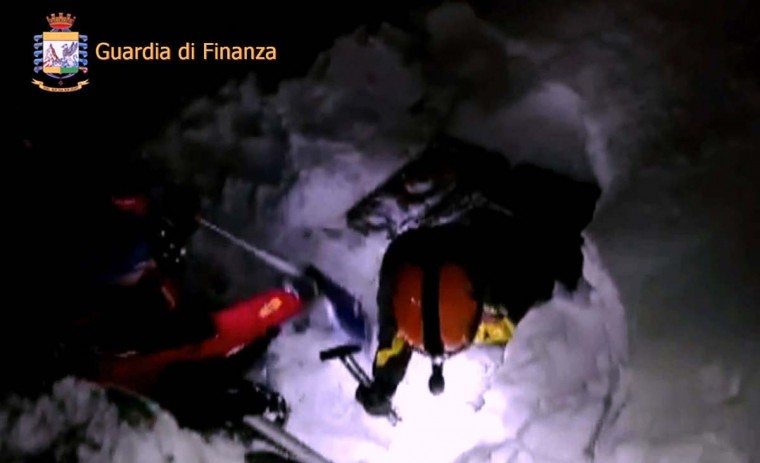 This image grab made from a video handout released by the Guardia di Finanza on January 19, 2017 shows rescue team members digging the snow at the Hotel Rigopiano engulfed by a powerful avalanche near the village of Farinfola, on the eastern lower slopes of the Gran Sasso mountain. Up to 30 people were feared to have died after an Italian mountain Hotel Rigopiano was engulfed by a powerful avalanche in the earthquake-ravaged center of the country. Italy's Civil Protection agency confirmed the Hotel Rigopiano had been engulfed by a six-feet high wall of snow and that emergency services were struggling to get ambulances and diggers to the site. (AFP PHOTO / Guardia di Finanza press office / Handout)