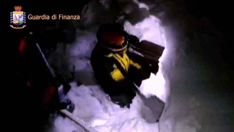 This image grab made from a video handout released by the Guardia di Finanza on January 19, 2017 shows a rescue team member digging the snow at the Hotel Rigopiano engulfed by a powerful avalanche near the village of Farinfola, on the eastern lower slopes of the Gran Sasso mountain. Up to 30 people were feared to have died after an Italian mountain Hotel Rigopiano was engulfed by a powerful avalanche in the earthquake-ravaged center of the country. Italy's Civil Protection agency confirmed the Hotel Rigopiano had been engulfed by a six-feet high wall of snow and that emergency services were struggling to get ambulances and diggers to the site. (AFP PHOTO / Guardia di Finanza press office / Handout)
