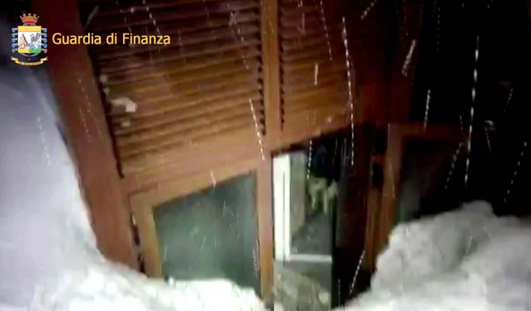 This image grab made from a video handout released by the Guardia di Finanza on January 19, 2017 shows the Hotel Rigopiano, near the village of Farinfola, on the eastern lower slopes of the Gran Sasso mountain, engulfed by a powerful avalanche. Up to 30 people were feared to have died after an Italian mountain Hotel Rigopiano was engulfed by a powerful avalanche in the earthquake-ravaged center of the country. Italy's Civil Protection agency confirmed the Hotel Rigopiano had been engulfed by a six-feet high wall of snow and that emergency services were struggling to get ambulances and diggers to the site. (AFP PHOTO / Guardia di Finanza press office / Handout)