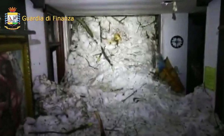 This image grab made from a video handout released by the Guardia di Finanza on January 19, 2017 shows a wall of snow engulfing the inside of the Hotel Rigopiano, near the village of Farindola, on the eastern lower slopes of the Gran Sasso mountain. Up to 30 people were feared to have died after an Italian mountain Hotel Rigopiano was engulfed by a powerful avalanche in the earthquake-ravaged center of the country. Italy's Civil Protection agency confirmed the Hotel Rigopiano had been engulfed by a (six-feet) high wall of snow and that emergency services were struggling to get ambulances and diggers to the site. (AFP PHOTO / Guardia di Finanza press office / Handout)