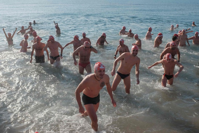 Swimmers participate in the traditional New Year day swim as part of the celebrations of the New Year at the Ostia Lido, Rome's seashore on January 1, 2017. (AFP PHOTO / Alberto PIZZOLI)