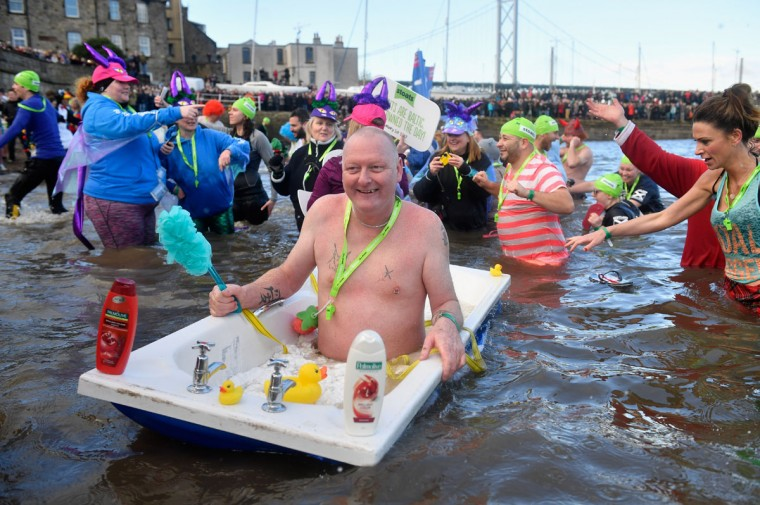 SOUTH QUEENSFERRY, SCOTLAND - JANUARY 01:  Members of the public wearing fancy dress in the water as they join around 1,000 New Year swimmers, many in costume, in front of the Forth Rail Bridge during the annual Loony Dook Swim in the River Forth on January 1, 2017 in South Queensferry, Scotland. Tens of thousands of people gathered last night in Edinburgh and other events across Scotland to see in the New Year at Hogmanay celebrations.  (Photo by Jeff J Mitchell/Getty Images)