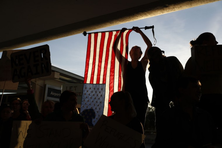 SAN FRANCISCO, CA - JANUARY 28: A demonstrator holds an American flag during a rally against muslim immigration ban at San Francisco International Airport on January 28, 2017 in San Francisco, California. President Donald Trump signed an executive order Friday that suspends entry of all refugees for 120 days, indefinitely suspends the entries of all Syrian refugees, as well as barring entries from seven predominantly Muslim countries from entering for 90 days. (Photo by Stephen Lam/Getty Images)