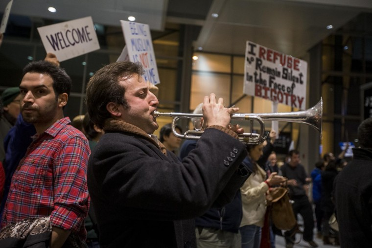 "BOSTON, MA - JANUARY 28: A protestor plays ""This Land Is Our Land"" on a trumpet during a demonstration against the new ban on immigration issued by President Donald Trump at Logan International Airport on January 28, 2017 in Boston, Massachusetts. President Trump signed an executive order that halted refugees and residents from predominantly Muslim countries from entering the United States. (Photo by Scott Eisen/Getty Images)"