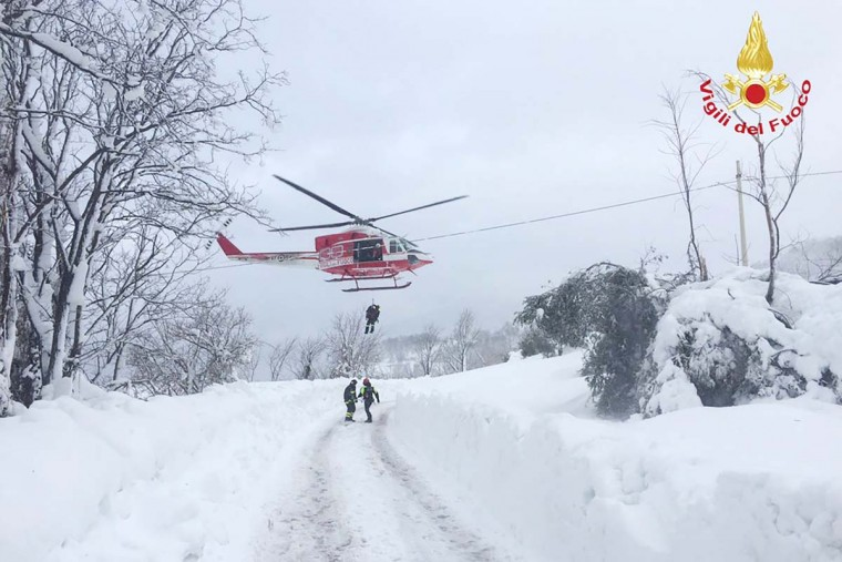 This handout image obtained on the Vigili del Fuoco twitter account on January 19, 2017 shows a rescue operation at the Hotel Rigopiano, near the village of Farindola, on the eastern lower slopes of the Gran Sasso mountain, engulfed by a powerful avalanche. Up to 30 people were feared to have died after an Italian mountain Hotel Rigopiano was engulfed by a powerful avalanche in the earthquake-ravaged center of the country. Italy's Civil Protection agency confirmed the Hotel Rigopiano had been engulfed by a (six-feet) high wall of snow and that emergency services were struggling to get ambulances and diggers to the site. (AFP PHOTO / Vigili del Fuoco / Handout)