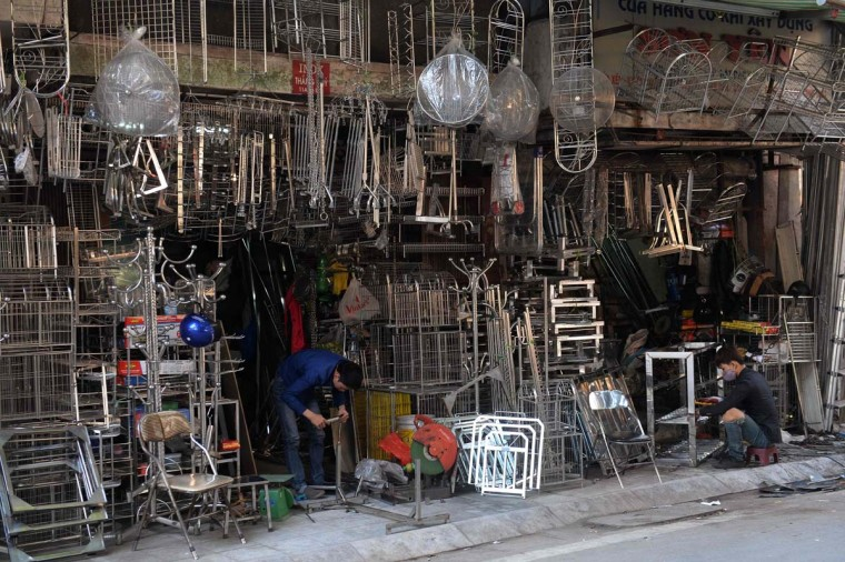 This picture taken on December 8, 2016 shows men working at metal houseware shops on Lo Ren street in downtown Hanoi. Sitting before a bright orange flame, Vietnamese blacksmith Nguyen Phuong Hung prods a fire pit with a long metal rod before he hammers, bends, and contorts glowing steel into a giant drill bit. Hung, who toils away in his tiny corner stall in downtown Hanoi, is the last remaining blacksmith on Hanoi's Lo Ren street, named after the masters of metal it was once known for. (HOANG DINH NAM/AFP/Getty Images)
