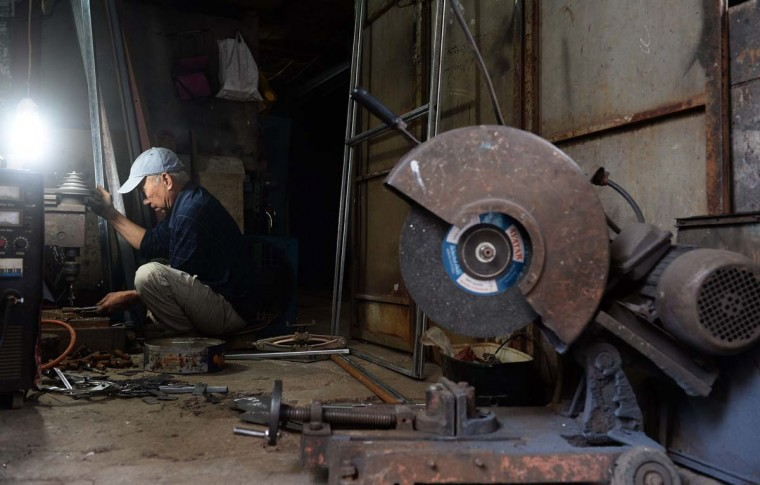 This picture taken on December 8, 2016 shows a man working inside a family-run mechanic workshop on Lo Ren street in downtown Hanoi. Sitting before a bright orange flame, Vietnamese blacksmith Nguyen Phuong Hung prods a fire pit with a long metal rod before he hammers, bends, and contorts glowing steel into a giant drill bit. Hung, who toils away in his tiny corner stall in downtown Hanoi, is the last remaining blacksmith on Hanoi's Lo Ren street, named after the masters of metal it was once known for. (HOANG DINH NAM/AFP/Getty Images)