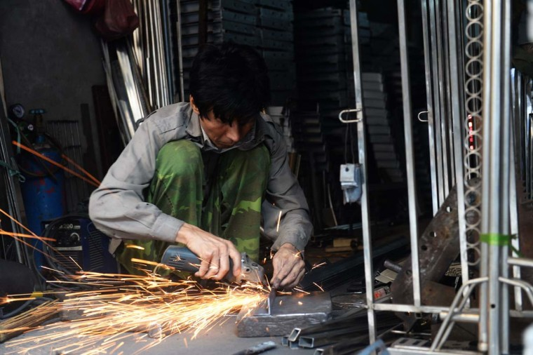 This picture taken on December 8, 2016 shows a man working at a family-run mechanic workshop on Lo Ren street in downtown Hanoi. Sitting before a bright orange flame, Vietnamese blacksmith Nguyen Phuong Hung prods a fire pit with a long metal rod before he hammers, bends, and contorts glowing steel into a giant drill bit. Hung, who toils away in his tiny corner stall in downtown Hanoi, is the last remaining blacksmith on Hanoi's Lo Ren street, named after the masters of metal it was once known for. (HOANG DINH NAM/AFP/Getty Images)