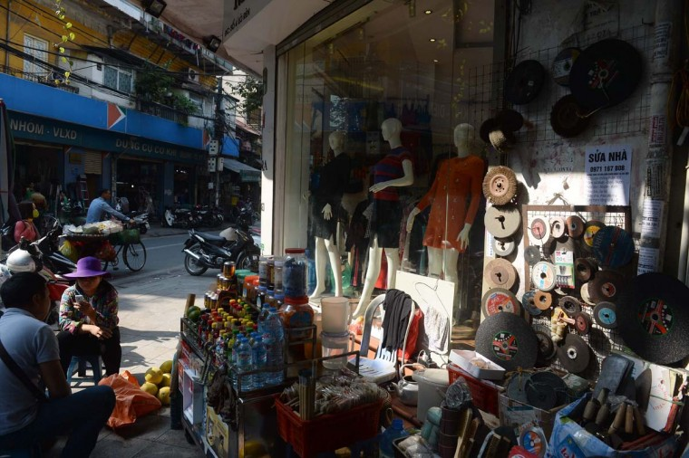 This picture taken on December 8, 2016 shows a tea vendor (2nd L) sitting in front of a former blacksmith workshop which has been turned into a clothing shop on Lo Ren street in downtown Hanoi. Sitting before a bright orange flame, Vietnamese blacksmith Nguyen Phuong Hung prods a fire pit with a long metal rod before he hammers, bends, and contorts glowing steel into a giant drill bit. Hung, who toils away in his tiny corner stall in downtown Hanoi, is the last remaining blacksmith on Hanoi's Lo Ren street, named after the masters of metal it was once known for. (HOANG DINH NAM/AFP/Getty Images)