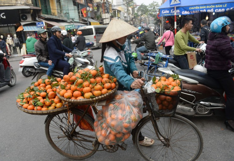 A street vendor hawks oranges along a street in downtown Hanoi on January 23, 2017, as Vietnamese prepare to celebrate the Lunar New Year or Tet later this week. Known locally as Tet, the celebration of the Lunar New Year is Vietnam's most important holiday and triggers a surge in consumption and travel ahead of an extended nationwide shutdown. (Hoang Dinh Nam/AFP/Getty Images)