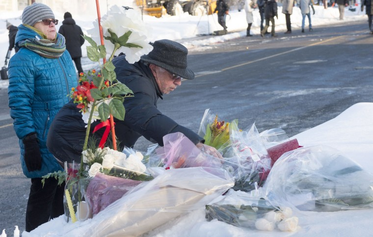 A couple places flowers near a mosque where a Sunday night shooting left multiple people dead, Monday, Jan. 30, 2017 in Quebec City. (Paul Chiasson/The Canadian Press via AP)