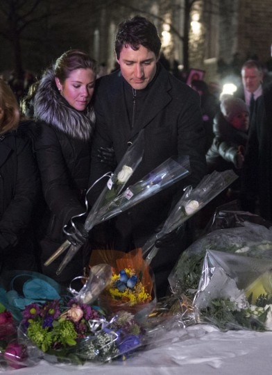 Canadian Prime Minister Justin Trudeau and his wife Sophie Gregoire Trudeau place flowers at a makeshift memorial during a vigil Monday, Jan. 30, 2017, for victims of Sunday's deadly shooting at a Quebec City mosque. (Chris Young/The Canadian Press via AP)