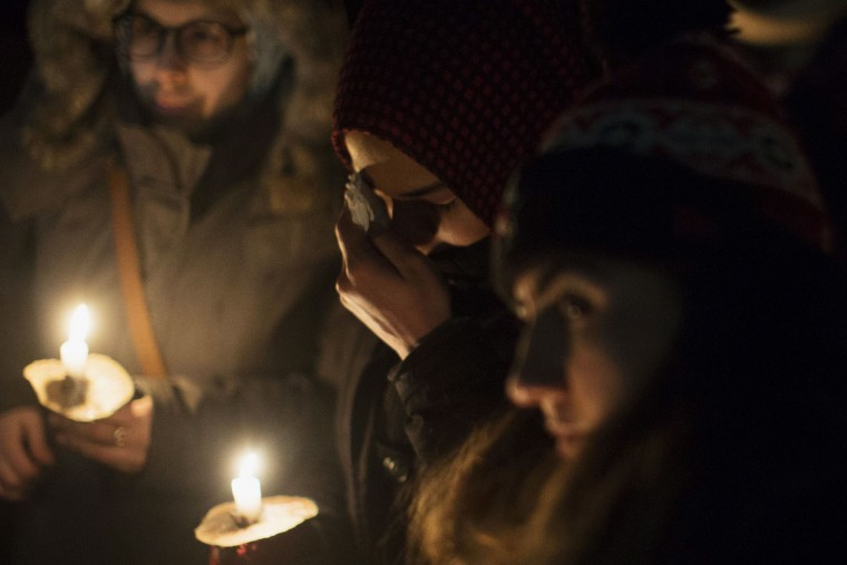 A woman wipes tears from her eye as people gather to observe a candlelight vigil in Toronto on Monday, Jan. 30, 2017, for victims of Sunday's deadly shooting at a Quebec City mosque. (Chris Young/The Canadian Press via AP)