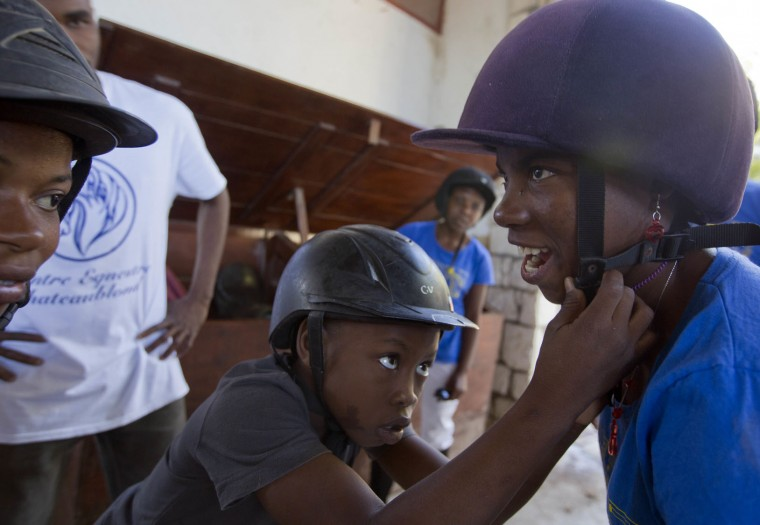 In this Jan. 11, 2017 photo, Judeley Hans Debel helps his friend Fabienne Charles with her helmet at the Chateaublond Equestrian Center in Petion-Ville, Haiti. Both are receiving free, therapeutic horse riding lessons at the center, which advocates say provides muscle and nerve stimulation to disabled youngsters. (AP Photo/Dieu Nalio Chery)