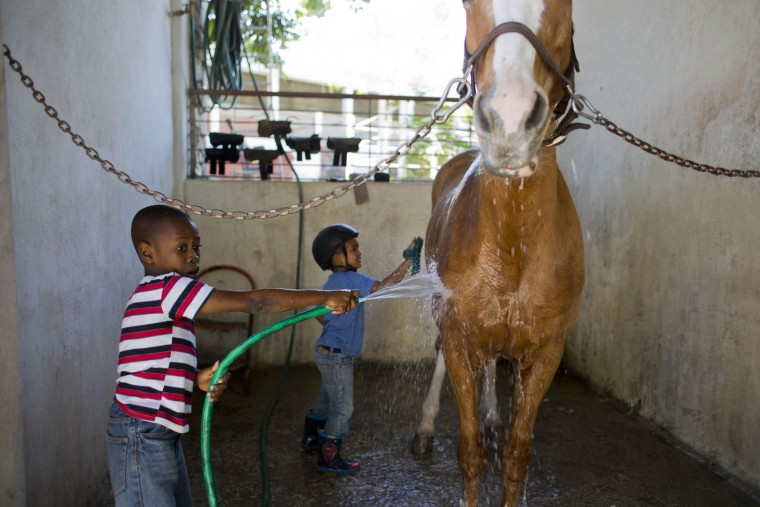 In this Jan. 7, 2017 photo, Judeley Hans Debel, who uses a prosthetic right leg, bathes Tic Tac after riding her at the Chateaublond Equestrian Center in Petion-Ville, Haiti. Judeley runs as fast as his prosthetic leg can take him when he arrives where a riding session with his favorite horse is the highlight of his week. (AP Photo/Dieu Nalio Chery)
