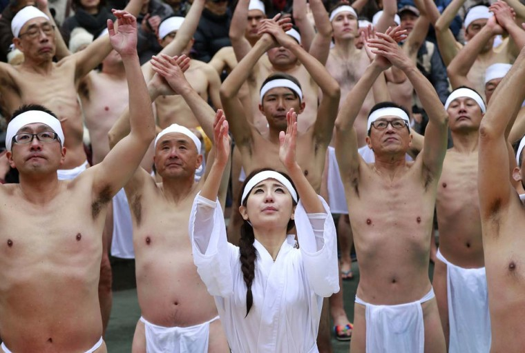 Japanese bathers exercise before dipping in a cold water tub with blocks of ice at a park by Teppozu Inari Shinto Shrine during a winter ritual in Tokyo, Sunday, Jan. 8, 2017. About 100 people gathered for the mid-winter event to pray for their healthy new year and displayed their perseverance. (AP Photo/Shizuo Kambayashi)