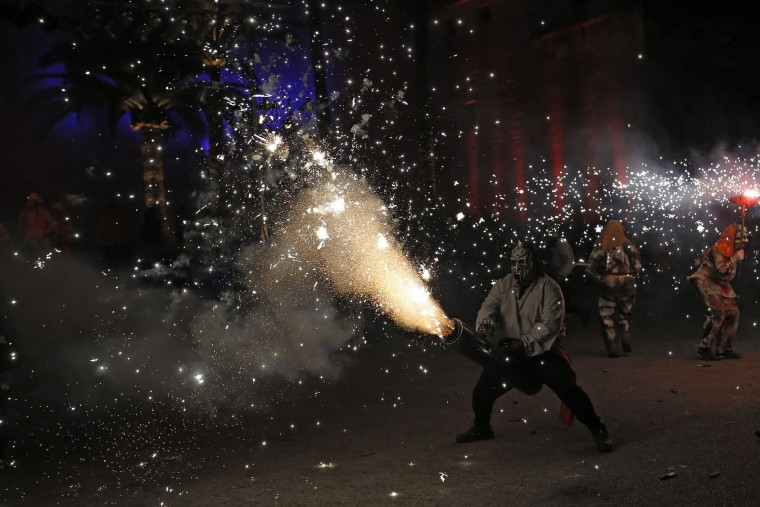 In this photo taken on Monday, Jan. 16, 2017, revelers dressed as demons called 'Dimonis' hold fireworks as they take part in a 'Correfoc' or 'run with fire' party during traditional celebrations in honor of Saint Anthony in Muro village in the Mediterranean island of Mallorca, Spain. Mixing pagan and religious traditions from medieval times, the fire and demon festivals are held in towns across the island of Mallorca each Jan. 16-17 to celebrate the day of Saint Anthony the Abbot, the patron saint of animals. (AP Photo/Francisco Seco)