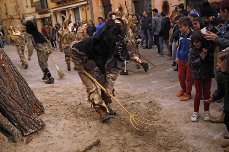 In this photo taken on Monday, Jan. 16, 2017, a reveler dressed as a demon called 'Dimonis' runs with a wooden fork after people to scare them during traditional celebrations in honor of Saint Anthony in Alcudia village at the Mediterranean island of Mallorca, Spain. Mixing pagan and religious traditions from medieval times, the fire and demon festivals are held in towns across the island of Mallorca each Jan. 16-17 to celebrate the day of Saint Anthony the Abbot, the patron saint of animals. (AP Photo/Francisco Seco)