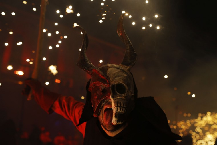 In this photo taken on Monday, Jan. 16, 2017, a reveler dressed as a demon called 'Dimonis' holds fireworks as he takes part in a 'Correfoc' or 'run with fire' party during traditional celebrations in honor of Saint Anthony in Muro village in the Mediterranean island of Mallorca, Spain. Mixing pagan and religious traditions from medieval times, the fire and demon festivals are held in towns across the island of Mallorca each Jan. 16-17 to celebrate the day of Saint Anthony the Abbot, the patron saint of animals. (AP Photo/Francisco Seco)