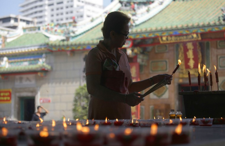 An ethnic Chinese Thai lights a candle before praying at the Leng Nuei Yee Chinese temple in Bangkok, Thailand, Tuesday, Jan. 24, 2017. Chinese New Year falls on Jan. 28, this year, marking the start of the Year of Rooster according to the Chinese lunar calendar. (AP Photo/Sakchai Lalit)