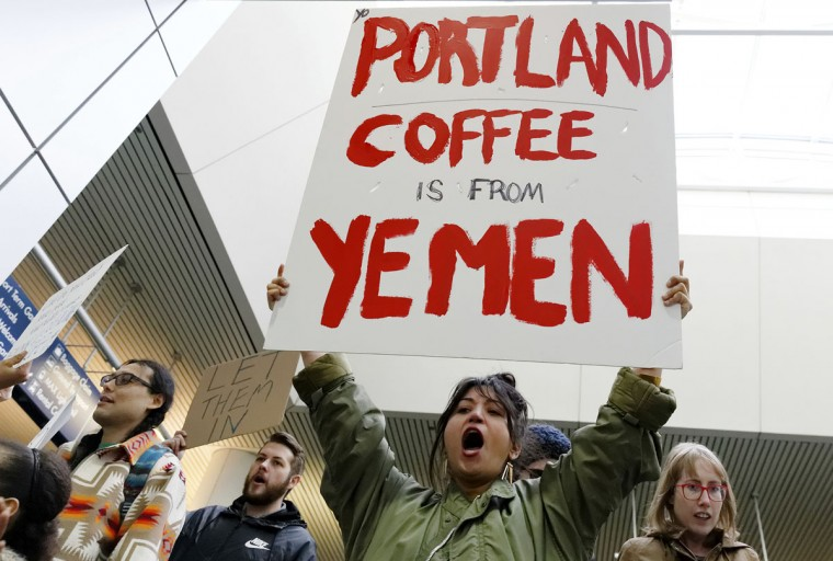 Lucia Martinez, who organized the rally, marches with others demonstrating in and around the main terminal at Portland International Airport, Saturday, Jan. 28, 2017, in Portland, Ore., to protest President Donald Trump's executive order barring nationals of seven Muslim-majority countries from entering the U.S. (Mike Zacchino/The Oregonian via AP)