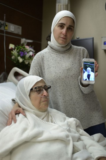 Nour Ulayyet holds her smartphone with a photo of her sister Sahar Algonaimi, who was not permitted to enter the United States, while comforting her mother Isaaf Jamal Eddin at Munster Community Hospital Saturday, Jan. 28, 2017, in Munster, Ind. Ulayyet of Valparaiso, Ind., said her sister, a Syrian living in Saudi Arabia who had a valid visa, was sent back after arriving from Riyadh at Chicago's O'Hare International Airport on Saturday and told she couldn't enter the U.S. to help care for their sick mother following President Donald Trump's executive order banning individuals from certain Muslim-majority countries from entering the U.S. (AP Photo/Paul Beaty)