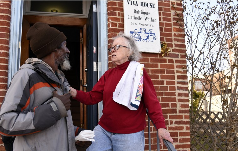 Jerry-Daniel Lewis, left, talks with Willa Bickham, right, on the front steps of Viva House, a West Baltimore soup kitchen that was founded 49 years ago by Catholic Worker husband and wife team Brendan Walsh and Willa Bickham. (Barbara Haddock Taylor/Baltimore Sun)