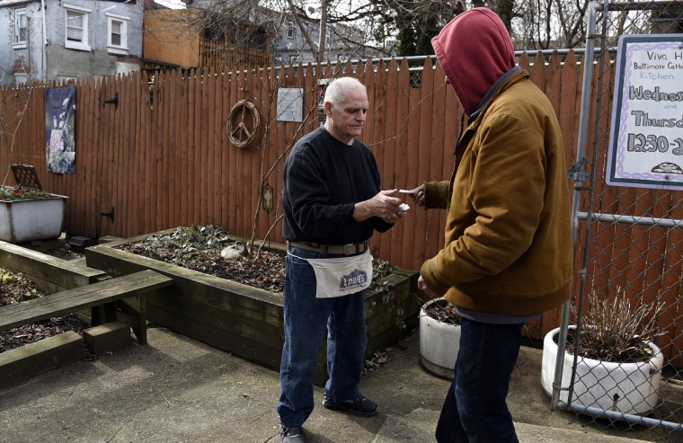 Brendan Walsh hands a ticket to a guest at Viva House, a West Baltimore soup kitchen that was founded 49 years ago by he and his wife Willa Bickham, who are Catholic Workers.  (Barbara Haddock Taylor/Baltimore Sun)
