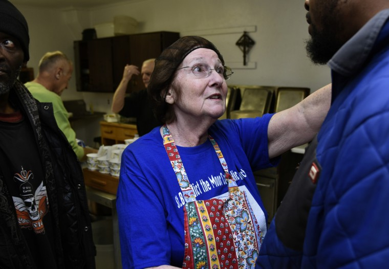 Volunteer Carol Rosen of Bowie, center, talks in the kitchen with a guest at Viva House, a West Baltimore soup kitchen that was founded 49 years ago by Catholic Worker husband and wife team Brendan Walsh and Willa Bickham. Ms. Rosen, who has been volunteering for around 10 years, bakes hundreds of cookies a week for the guests.  (Barbara Haddock Taylor/Baltimore Sun)