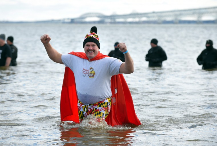 Bruce Bouch, of Gamber, with the Maryland State Fireman's  Association, enters the bay during 21st Annual Maryland State Police Polar Bear Plunge and PlungeFest held at Sandy Point State Park to raise money for Special Olympics Maryland.  (Lloyd Fox/Baltimore Sun)