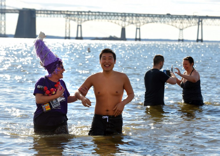 Tressa Andrews of Forest Hill stands in the bay with Special Olympic Athlete, Danny Grau of Fallston during the 21st Annual Maryland State Police Polar Bear Plunge and PlungeFest. (Lloyd Fox/Baltimore Sun)