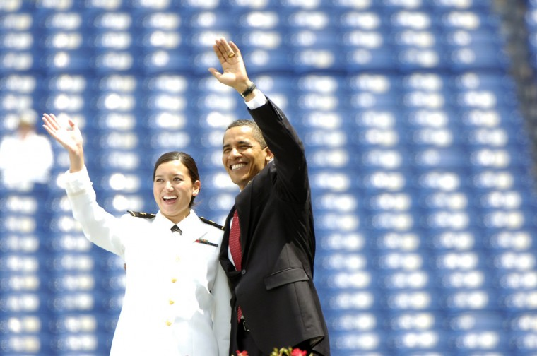 May 22, 2009 -- Brittany Young, left, the last graduate to cross the stage poses for pictured with President Barak Obama while waving to her family  before receiving her diploma. President Obama gave the graduation address at the United States Naval Academy Class of 2009 Graduation and Commissioning Ceremonies. (Kenneth K. Lam/The Baltimore Sun)