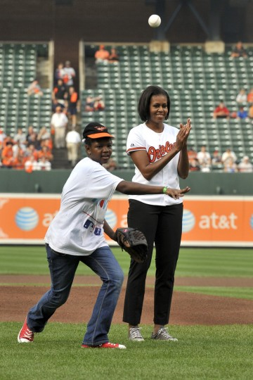 July 20, 2010 -- First Lady Michelle Obama (r) claps her hands as Christina McCray throws out the ceremonial first pitch before Baltimore Orioles - Tampa Bay Rays baseball game.  (Lloyd Fox/Baltimore Sun)