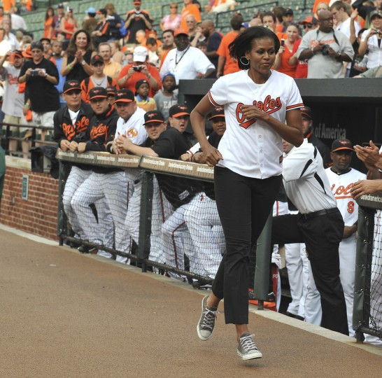 July 20, 2010 -- First Lady Michelle Obama running off the field after shakes the hands of the Orioles  before Baltimore Orioles - Tampa Bay Rays baseball game.   (Lloyd Fox/Baltimore Sun)