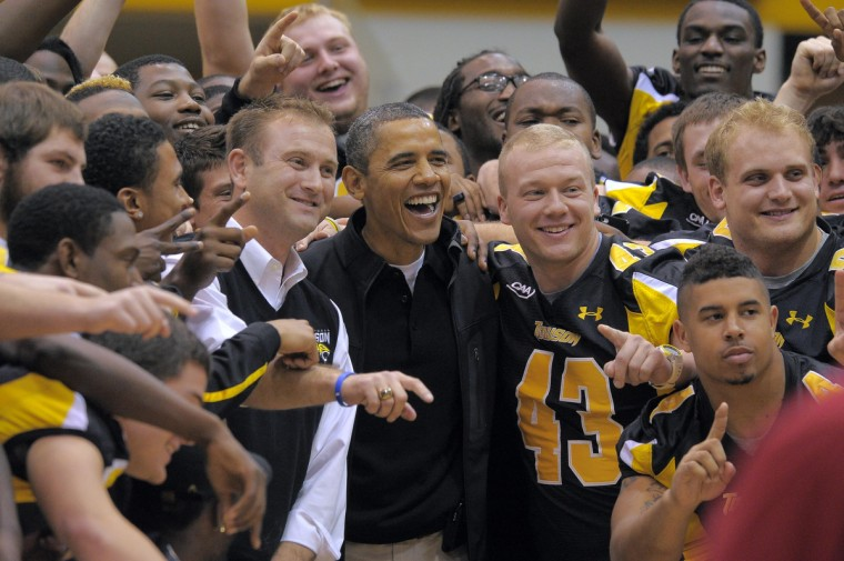 November 26, 2011 -- President Barack Obama (center) poses with football head coach Rob Ambrose (left) and his team, winners of the CAA championship during halftime festivities as the Towson Tigers host the Oregon State Beavers in the men's college basketball home opener at the Towson Center. (Karl Merton Ferron/Baltimore Sun)