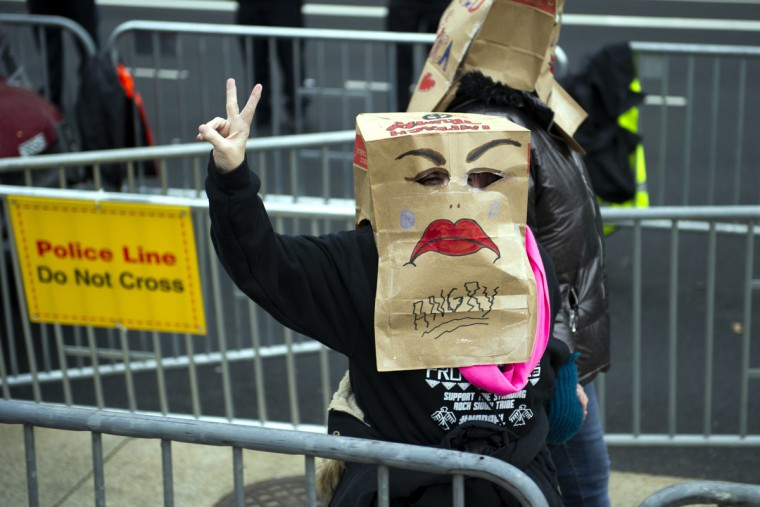 A protestor flashes the peace sign while walking along the presidential inaugural parade route in Washington, Friday, Jan. 20, 2017. (Cliff Owen/AP Photo)