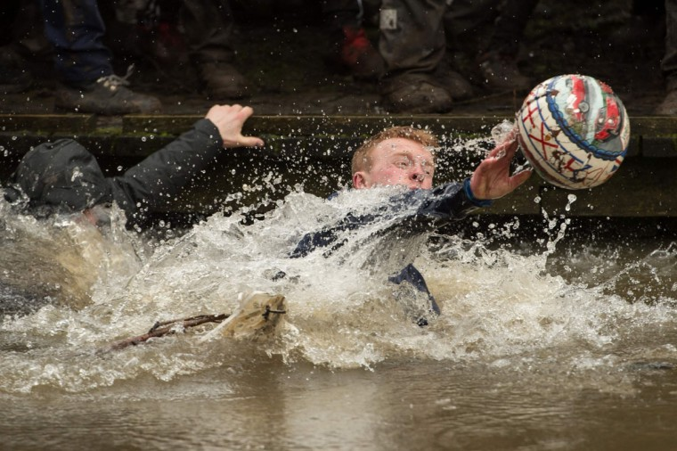 Competitors reach for the ball during the annual Royal Shrovetide Football Match in Ashbourne, northern England, on February 28, 2017. The mass-participation ball game involves two teams, whose players are defined by which side of a small brook that bisects the town they were born, aiming to score a goal, which are some three miles apart. The game, which has very few rules, is played over two 8 hour periods on Shrove Tuesday and Ash Wednesday. Royal Shrovetide Football is believed to have been played annually in Ashbourne since 1667. (AFP PHOTO / OLI SCARFF)