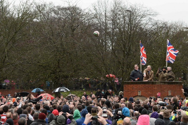 The ball is 'turned up' to start the annual Royal Shrovetide Football Match in Ashbourne, Derbyshire, England on February 28, 2017 between the two opposing team's, the Up'ards and the Down'ards. The mass-participation ball game involves two teams, whose players are defined by which side of a small brook that bisects the town they were born, aiming to score a goal, which are some three miles apart. The game, which has very few rules, is played over two 8 hour periods on Shrove Tuesday and Ash Wednesday. Royal Shrovetide Football is believed to have been played annually in Ashbourne since 1667. (AFP PHOTO / Oli SCARFF)