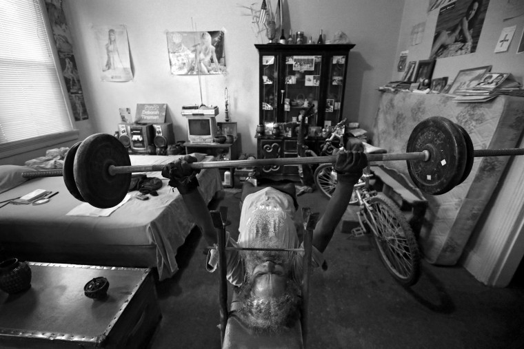 "Keith Boissiere bench presses in his bedroom on November 2, 2016 in Baltimore, Maryland. The 'Running Man' lives in solitude in a small West Baltimore apartment where his bedroom functions as his: dining area, weight room and sleeping quarters. Fitness model posters line the walls that serve as daily inspiration. ""I admire them and the way they take care of their bodies,"" Boissiere said. He says running doesn't support all the muscles in the body, so he routinely weight lifts. ""It's about having overall fitness, not concentrating on this while you neglect that,"" Boissiere said. (Patrick Smith/Getty Images)"