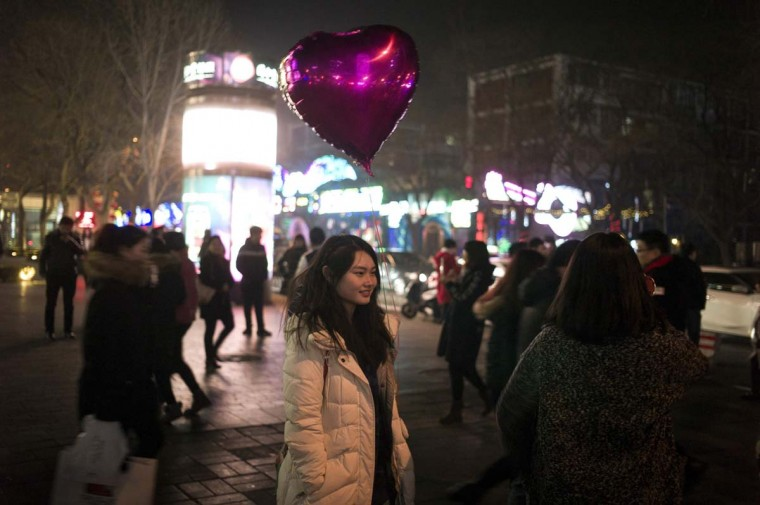 A pedestrian holds a heart-shaped balloon as she walks during Valentine's Day on a street in Beijing on February 14, 2017. A Pakistani court has banned public celebrations of Valentine's Day in the capital Islamabad while Indonesian students plan to spurn the event, as the festival of love gets a chilly reception in parts of Asia. (FRED DUFOUR/AFP/Getty Images)