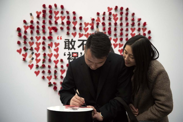 A couple write on a heart-shaped sticker at a shopping mall on Valentine's Day in Beijing on February 14, 2017. (NICOLAS ASFOURI/AFP/Getty Images)