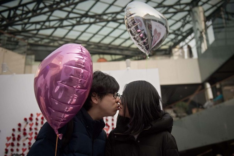A couple kiss as they walk around a shopping mall on Valentine's Day in Beijing on February 14, 2017. (NICOLAS ASFOURI/AFP/Getty Images)