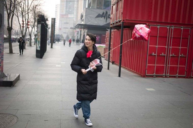 A man, carries a heart-shaped balloon as is distributes promotional material for a shop while walking during Valentine's Day on a street in Beijing on February 14, 2017. A Pakistani court has banned public celebrations of Valentine's Day in the capital Islamabad while Indonesian students plan to spurn the event, as the festival of love gets a chilly reception in parts of Asia. (FRED DUFOUR/AFP/Getty Images)