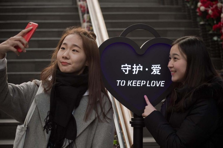 "Two friends take a selfie next to a heart-shaped sign that reads ""to keep love"" on Valentine's Day in Beijing on February 14, 2017. (NICOLAS ASFOURI/AFP/Getty Images)"