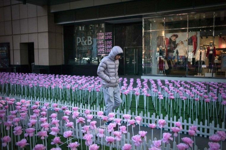 A pedestrian walks through a floral display during Valentine's Day on a street in Beijing on February 14, 2017. A Pakistani court has banned public celebrations of Valentine's Day in the capital Islamabad while Indonesian students plan to spurn the event, as the festival of love gets a chilly reception in parts of Asia. (FRED DUFOUR/AFP/Getty Images)