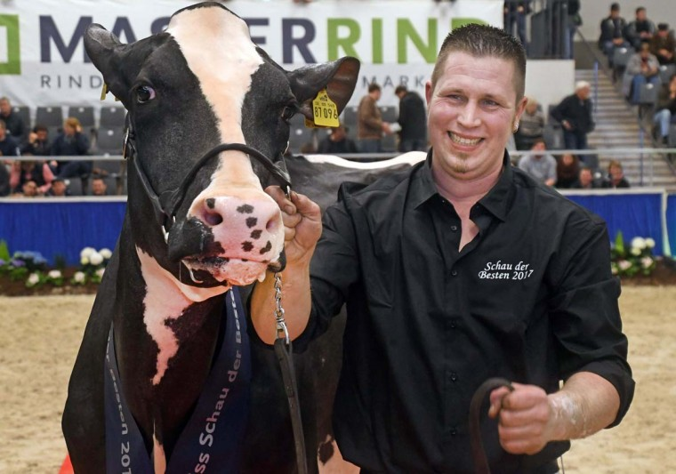 """Farmer Henrik Wille smiles as he presents his cow """"Madame"""" after she won the """"Schau der Besten"""" (Show of the Best) dairy cow beauty pageant on February 23, 2017 in Verden an der Aller, northwestern Germany. (CARMEN JASPERSEN/AFP/Getty Images)"""